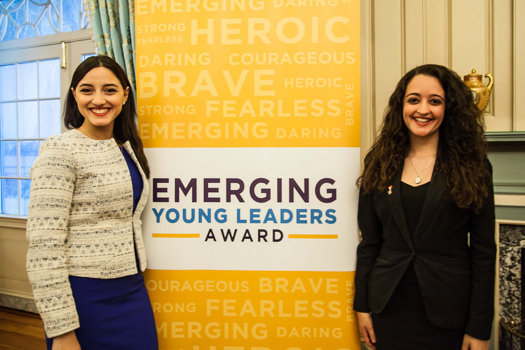Two Ladies Next To Emerging Young Leaders Award Display
