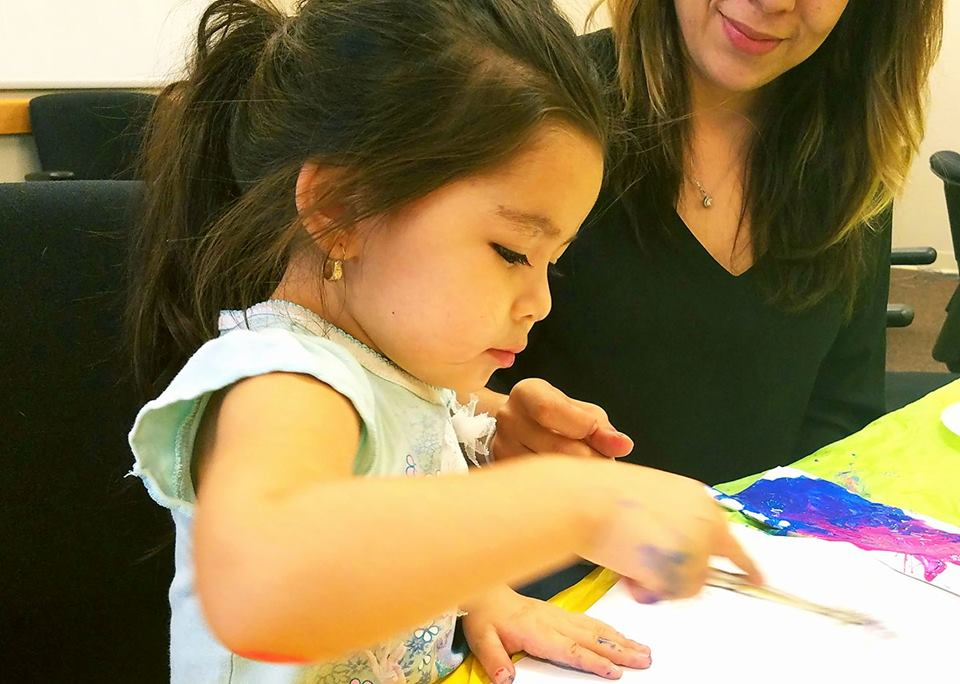 Child creating finger paint artwork